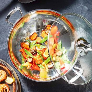 Wokpan gevuld met ingrediënten en glazen deksel